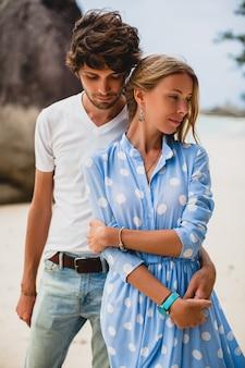 休暇中に熱帯のビーチで恋のスタイリッシュな流行に敏感な若いカップル