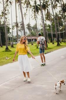 Молодая стильная хипстерская влюбленная пара на отдыхе с собакой и скейтбордом, веселится, романтично, солнцезащитные очки в красочном стиле