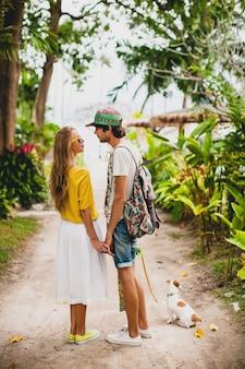 犬とスケートボードとの休暇に恋にスタイリッシュな流行に敏感な若いカップル