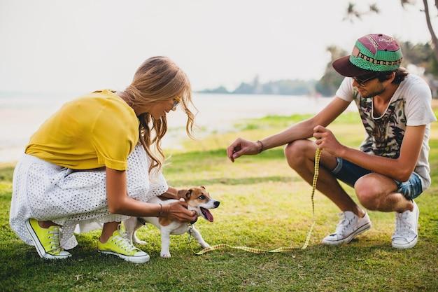 Молодая стильная хипстерская влюбленная пара гуляет и играет с собакой на тропическом пляже
