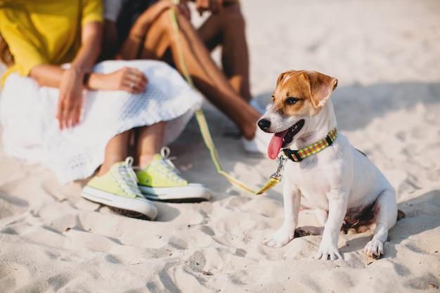 산책과 열 대 해변에서 강아지와 함께 연주 사랑에 젊은 세련된 힙 스터 커플