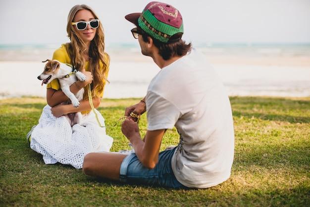 Молодая стильная хипстерская влюбленная пара гуляет, играя собачьим щенком джек рассел, тропический пляж, крутой наряд, романтическое настроение, веселится, солнечный, мужчина женщина вместе