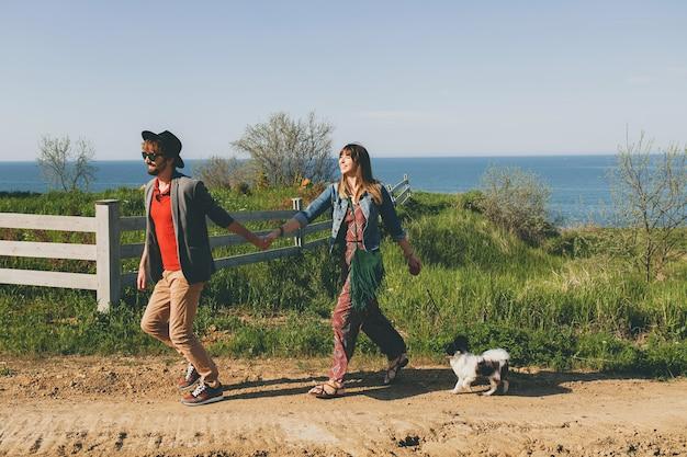Молодая стильная хипстерская влюбленная пара гуляет с собакой в сельской местности, бегает, веселится