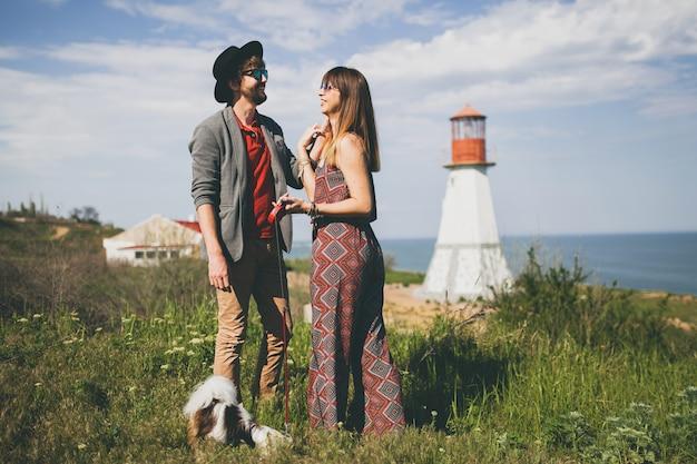 Молодая стильная хипстерская влюбленная пара гуляет с собакой в сельской местности