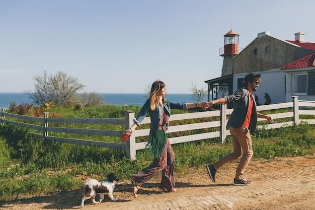 田舎で犬を連れて歩いて恋にスタイリッシュな流行に敏感な若いカップル