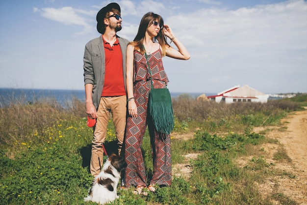 시골에서 강아지와 함께 산책하는 사랑에 젊은 유행 hipster 부부