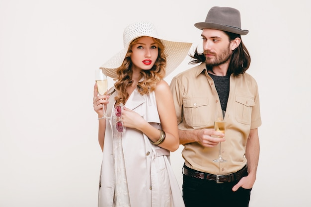 Young stylish hipster couple in love, holding glasses and drinking champagne