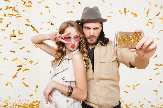 Young stylish hipster couple in love making self photo, celebrating disco party, having fun