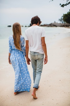 Coppia giovane elegante hipster in amore sulla spiaggia tropicale durante le vacanze