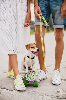 Young stylish hipster couple in love on vacation with dog and skateboard, having fun