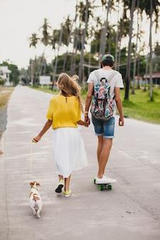 Giovane coppia hipster alla moda innamorata in vacanza con cane e skateboard, divertendosi
