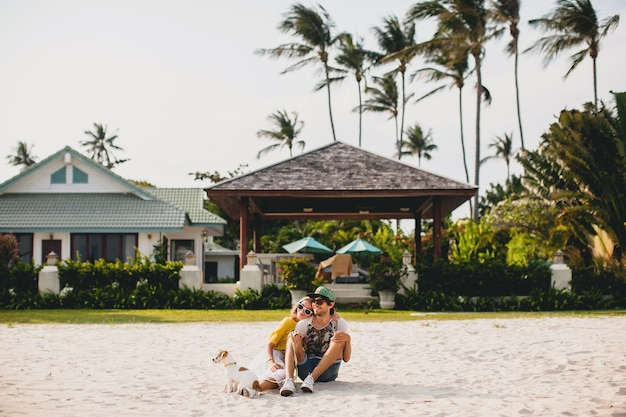 Young stylish hipster couple in love walking playing dog puppy jack russell, tropical beach, cool outfit, romantic mood, having fun, sunny, man woman together, horizontal, vacation, house home villa