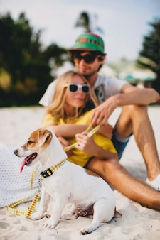 Young stylish hipster couple in love walking and playing with dog in tropical beach, cool outfit, romantic mood, having fun, sunny, man woman together, horizontal, vacation, house home villa