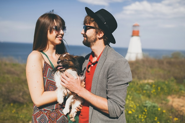 Young stylish hipster couple in love walking with dog in countryside