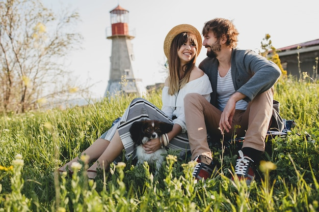 Young stylish hipster couple in love with dog in countryside, sitting in the grass