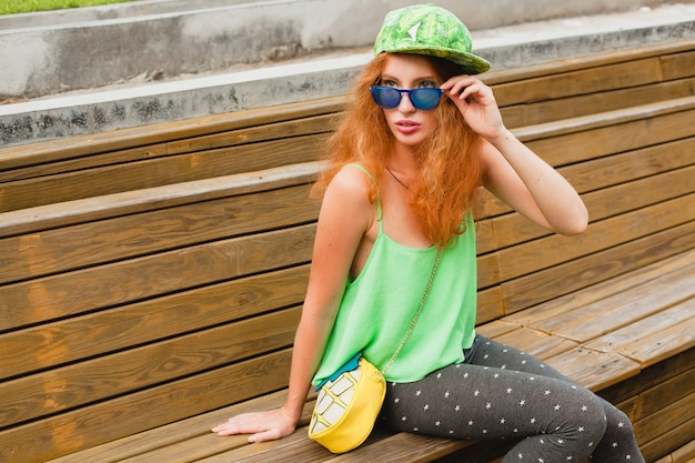 Giovane donna alla moda hipster allo zenzero, seduta su una panchina, berretto verde, leggings, borsa, occhiali da sole, divertimento, abbigliamento alla moda, vestito di moda, stile adolescente urbano