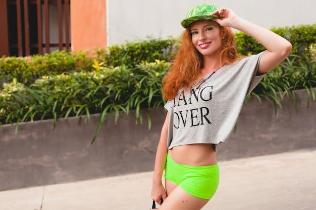 Giovane donna alla moda hipster allo zenzero, camminando in strada, berretto verde, t-shirt oversize grigia, divertirsi, abbigliamento alla moda, vestito di moda, stile adolescente urbano, zaino, viaggiatore