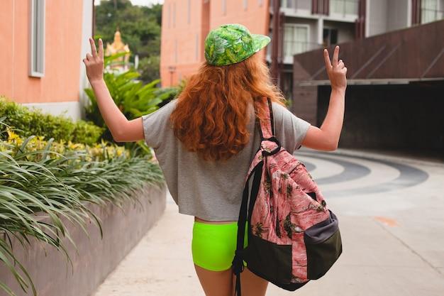 Giovane donna alla moda hipster allo zenzero, camminando in strada, berretto verde, abbigliamento alla moda, abbigliamento alla moda, stile adolescente urbano, zaino, viaggiatore, vista dal retro, che mostra segno di pace,