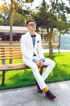 Young stylish hipster guy sitting on the bench, at city park, wearing trendy classic white suit, denim shirt and sunglasses. outdoor fashion portrait.