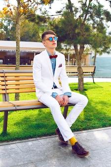 トレンディなクラシックな白いスーツ、デニムシャツ、サングラスを身に着けている都市公園のベンチに座っている若いスタイリッシュな流行に敏感な男。アウトドアファッションの肖像画。