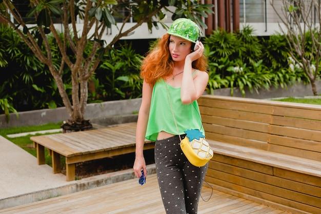 若いスタイリッシュなヒップスター幸せな生姜の女性、音楽を聴いて、ヘッドフォン、緑の帽子、笑顔、変な顔をクローズアップ、楽しんで、都会的なスタイル