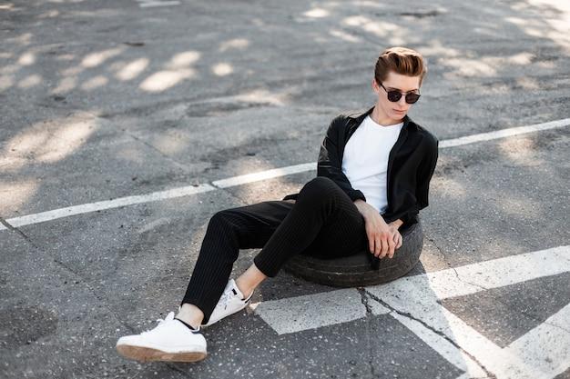 우아한 검은 셔츠에 유행 헤어 스타일을 가진 젊은 유행 hipster 남자