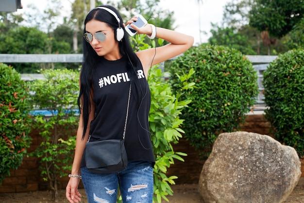 Giovane donna alla moda hipster in maglietta nera, jeans, ascoltare musica in cuffia, divertirsi, posa, divertente, sorridente