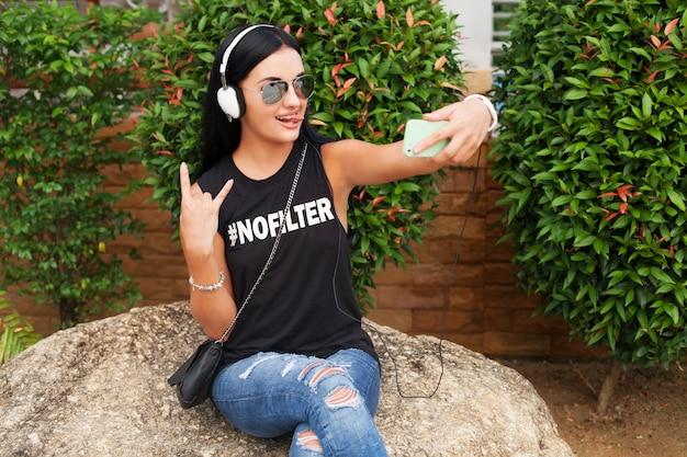 Giovane donna alla moda hipster in maglietta nera, jeans, ascoltare musica in cuffia, divertirsi, posare, scattare foto selfie sul telefono, mostrando il segno di pace, espressione del viso divertente