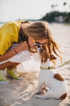 Young stylish hipster woman holding walking playing dog puppy jack russell, tropical park, smiling and have fun, vacation, sunglasses, cap, yellow shirt, beach sand