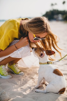 Young stylish hipster woman holding walking and playing with dog in tropical park, smiling and have fun