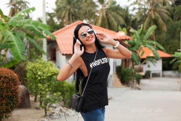 Молодая стильная хипстерская женщина в черной футболке, джинсах, слушает музыку в наушниках, веселится, гуляет по улице, летние каникулы, наслаждается