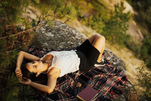 山の岩の上に横たわっている若いスタイリッシュな流行に敏感な女性。
