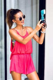 トレンディなビンテージカメラでselfieを作る若いスタイリッシュな流行に敏感な女性、笑顔のポーズと楽しい時を過します。