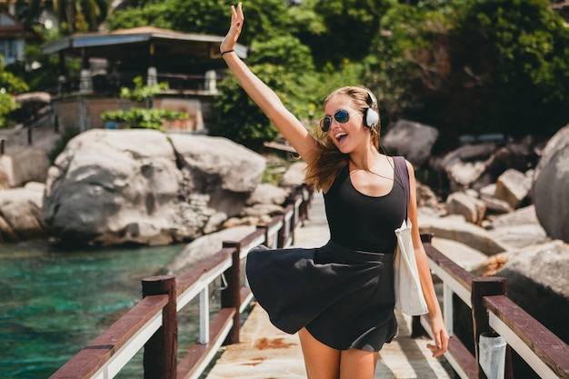 若いスタイリッシュな流行に敏感な女性のポジティブな気分、幸せな笑顔、世界中を旅する、サングラス、ヘッドフォン、音楽を聴く、熱帯の夏休み、スカート、自由を楽しむ、軽薄、セクシー