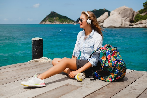 Young stylish hipster woman traveling around the world, sitting on the pier, aviator sunglasses, headphones, listening to music, vacation, backpack, denim shirt, happy, tropical island lagoon