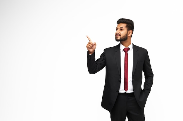 Young, stylish indian manager in a classic suit pointing his finger on a white isolated background, copy space for text.