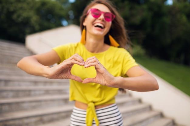 Молодая стильная смеющаяся женщина веселится в городском парке, улыбается веселое настроение, носит желтый топ, розовые солнцезащитные очки, модную тенденцию в летнем стиле, показывает знак сердца