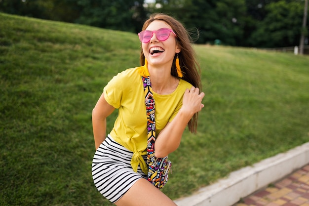 都市公園で楽しんで、陽気な気分を笑顔、黄色のトップ、ストライプのミニスカート、ピンクのサングラス、夏のスタイルのファッショントレンドを身に着けている若いスタイリッシュな笑う女性