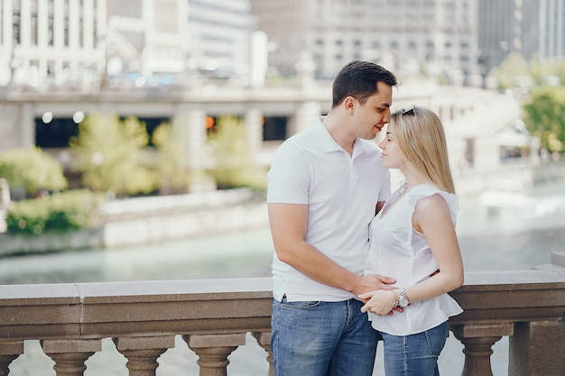 Young and stylish lovers couple in white t-shirts and blue jeans standing in a big city
