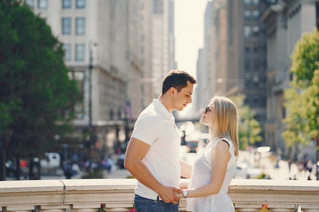 Young and stylish lovers couple in white t-shirts and blue jeans walking in a big city