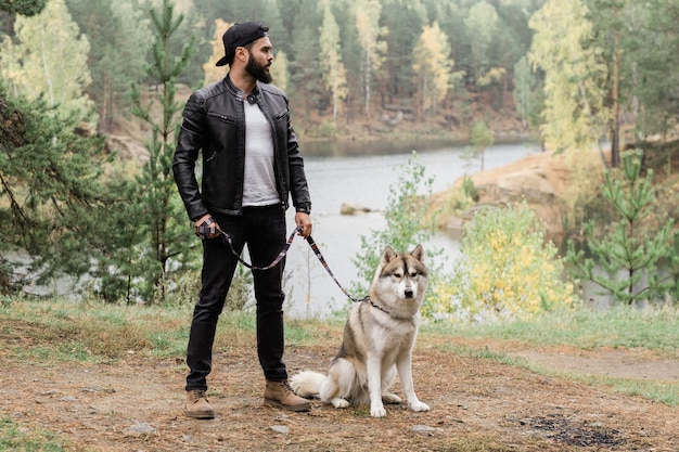 Young stylish man in black leather jacket and jeans standing on footpath in the forest or park while holding leash of his pet