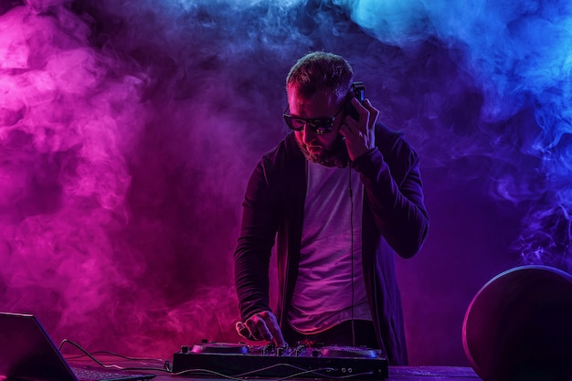 Young stylish man in glasses posing behind mixing console on colored smoke studio