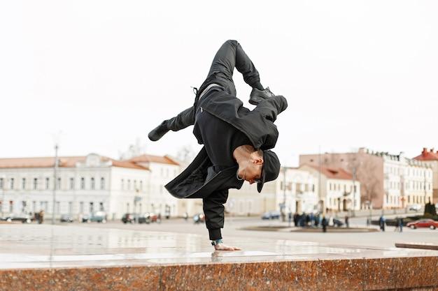 Молодой стильный мужчина в черной одежде танцует в городе