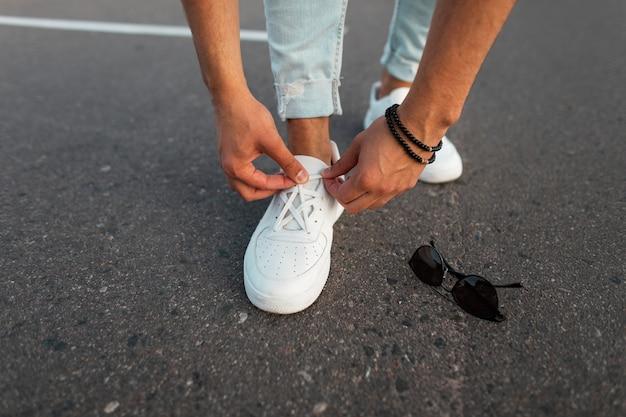 Молодой стильный мужчина в синих джинсах в кожаных белых модных туфлях стоит на дороге рядом с солнцезащитными очками и поправляет шнурки. модные мужские кроссовки и аксессуары. крупный план.