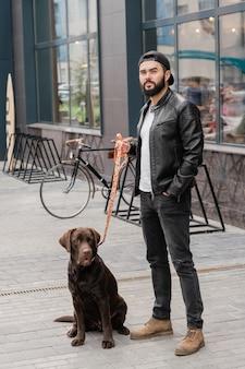 Молодой стильный мужчина в повседневной одежде, стоящий на троттуаре во время холода со своим милым питомцем в городской среде