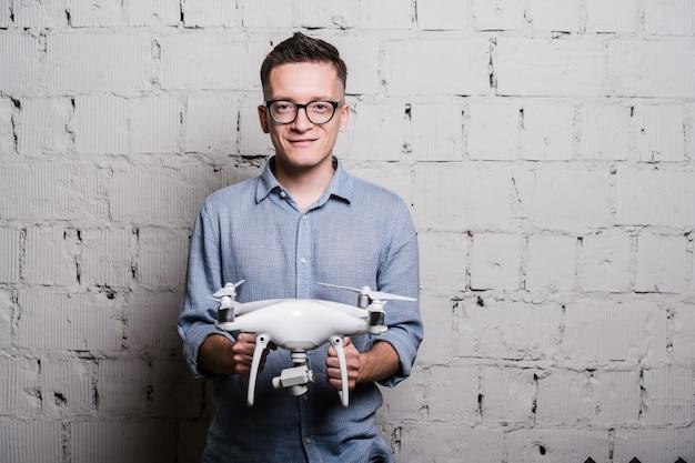 灰色のレンガの壁にquadcopterドローンを保持しているメガネのスタイリッシュな若者
