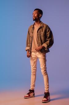 네온 불빛에 그라데이션 벽에 고립 된 현대 거리 스타일 복장에 세련 된 젊은이보기 책 음악가 공연에 아프리카 계 미국인 유행 모델