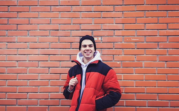 A young stylish man in a jacket with a backpack smiles against a red brick wall