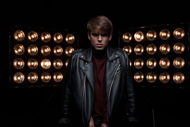 Young stylish man in leather cool black jacket in red golf in stylish trousers, posing in a dark studio against the background of electric bright orange light bulbs. attractive guy star