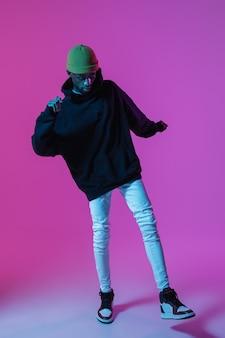 Giovane uomo elegante in abito moderno stile strada isolato sulla parete sfumata in luce al neon modello alla moda afroamericano in look book musicista esibendosi